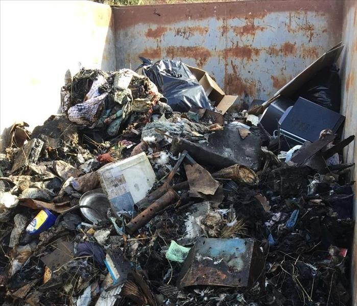 burned pile of debris in dumpster