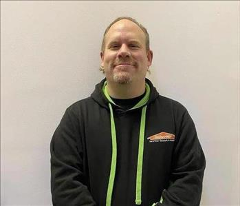 smiling man in black SERVPRO jacket looking at camera